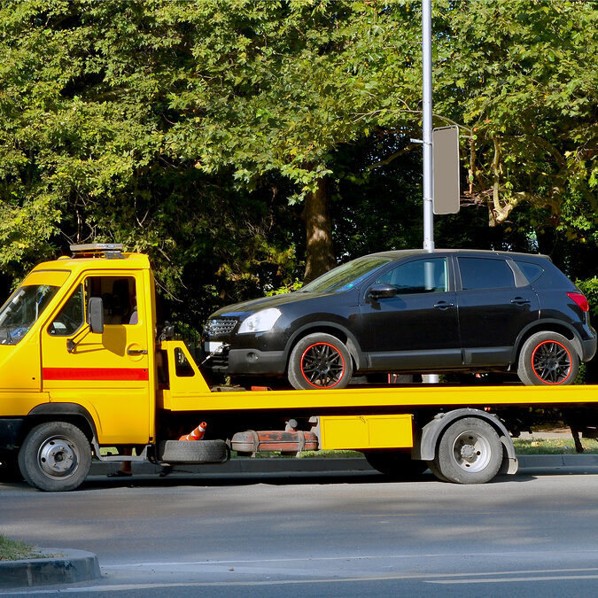 black car is loaded on a yellow car tow truck on a city street